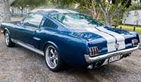 Rear left quarter view Blue Shelby 1965 Mustang Fastback with Wimbledon white lemans stripes