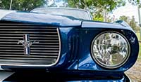 Right headlight and chrome detail Blue Shelby 1965 Mustang muscle car