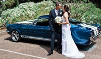 Wedding couple posing for photo's along side their East Coast hired Mustang Fastback