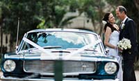 Front View Blue Shelby 1965 Mustang Fastback with newly-weds holding the bride's bouquet